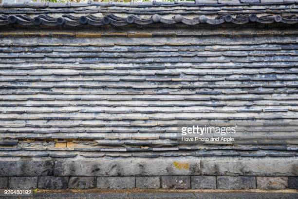 Wall with stacked roof tiles