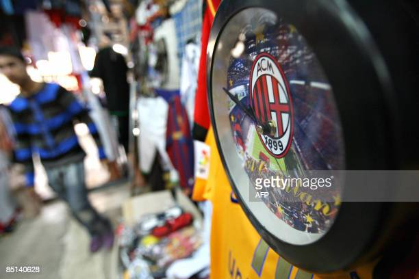 A wall with the AC Milan football club logo hangs on a wall at a sports shop in central Baghdad on February 27 2009 The clock which costs some 4 US...