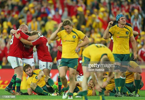Wallabies captain James Horwill and Michael Hooper look dejected as the Lions celebrate victory at the final whistle during the International Test...