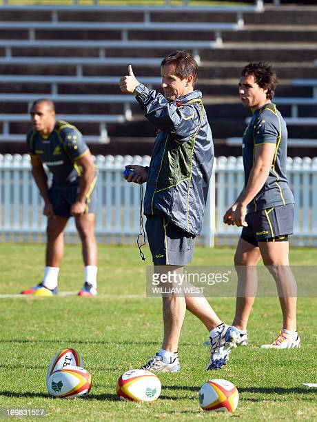 Wallabies coach Robbie Deans gestures as halfbacks Will Genia and Nick Phipps look on during the rugby team's first training session in Sydney on...