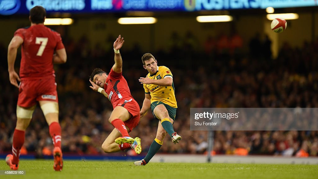 Wallabies fly half Bernard Foley kicks a drop goal despite the attentions of Mike Phillips during the Autumn international match between Wales and Australia at Millennium Stadium on November 8, 2014 in Cardiff, Wales.