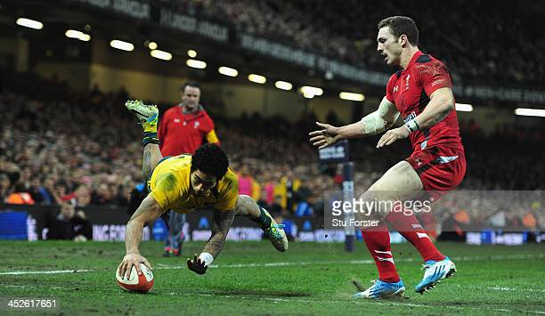 Wallabies wing Joe Tomane dives over to score despite the attentions of George North of Wales during the International match between Wales and...