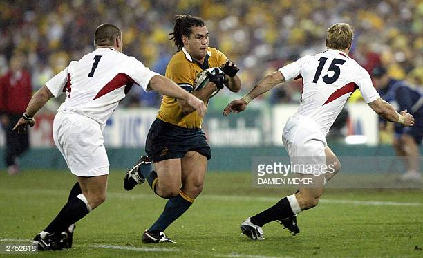 Wallaby flanker George Smith tries to go through English fullback Josh Lewsey and English prop Trevor Woodman during the Rugby World Cup final...