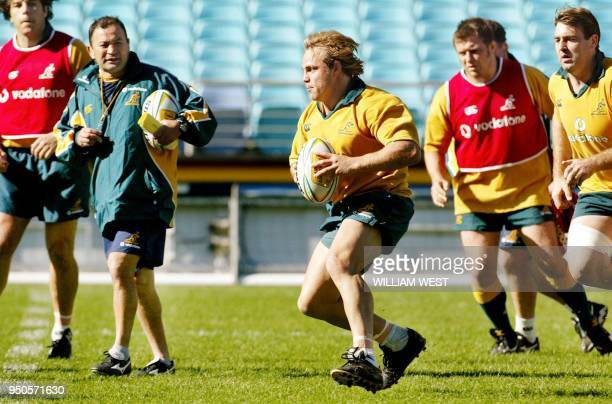 Wallaby player Phil Waugh is watched by coach as he leads a charge upfield as they prepare at Stadium Australia 13 June 2003 for their match against...