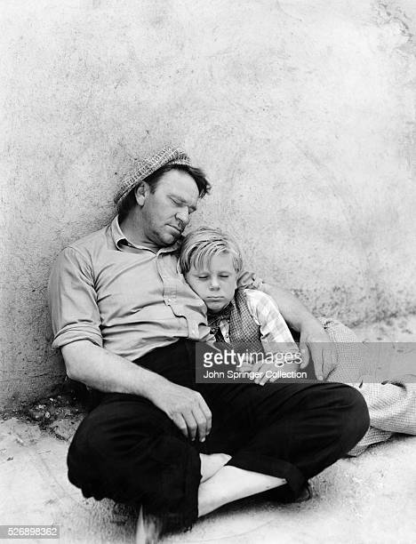 Wallace Beery and Jackie Cooper take a nap between scenes during filming of the 1931 film The Champ