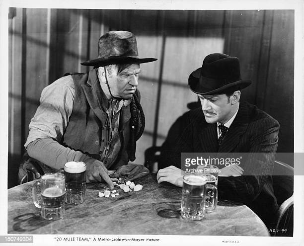Wallace Beery showing rocks to Douglas Fowley over beers in a scene from the film '20 Mule Team' 1940