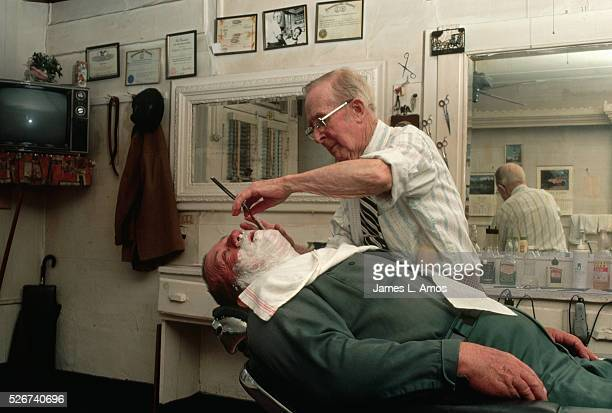 Wallace 'Tig' Jester continues to cut hair shave and chat with customers after 62 years of working in this barbershop in Chincoteague Virginia USA
