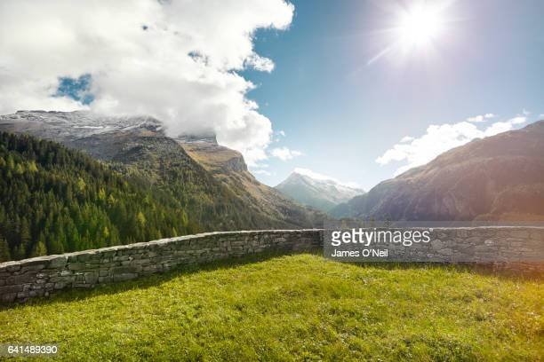 walled off grass paddock with background mountain ranges - swiss alps stock pictures, royalty-free photos & images