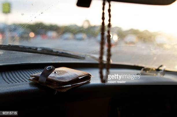 wallet and sunglasses on car dashboard
