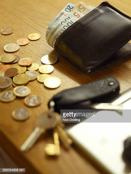 Wallet, loose coins and keys on table, close-up