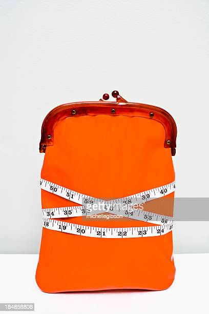 Wallet wrapped in tape measure showing a financial diet