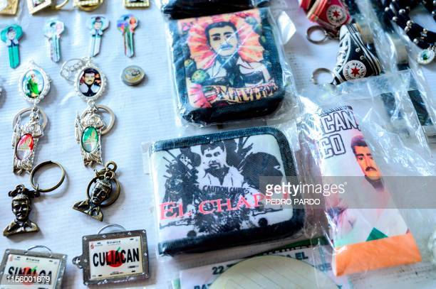 Wallets and pendants bearing the image of Mexican drug lord Joaquin El Chapo Guzman are displayed for sale at a store next to the narcosaint Jesus...
