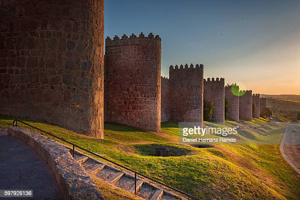 walls of avila at sunset. fortified building. fence surrounding the city - avila stock photos and pictures