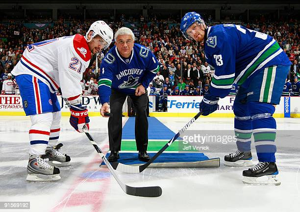 Wally Buono the alltime winningest coach in the CFL drops the puck in the ceremonal faceoff with Henrik Sedin of the Vancouver Canucks and Brian...