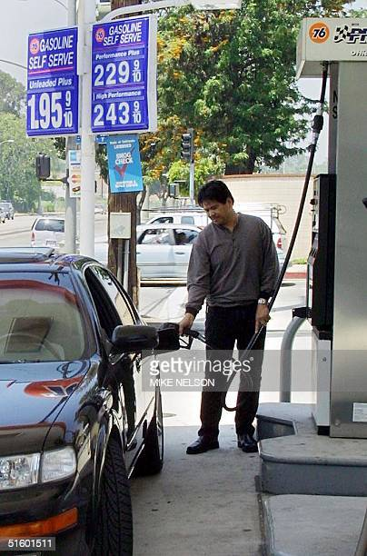 Wally Dizon pumps gas 09 May 2001 at a downtown Los Angeles gas station where selfservice prices for a gallon of gasoline range from USD 195 USD 243...