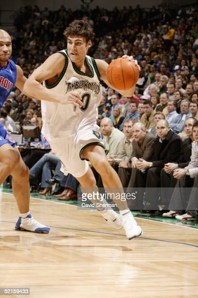 Wally Szczerbiak of the Minnesota Timberwolves drives around Darvin Ham of the Detroit Pistons during the game at Target Center on January 24 2005 in...