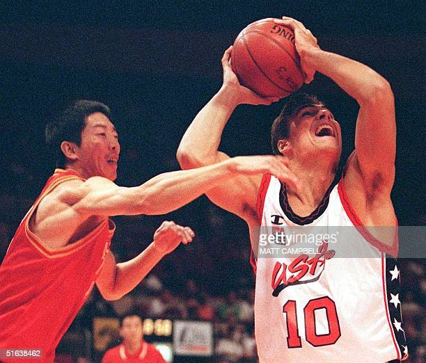 Wally Szczerbiak of the US tries to keep the ball away from Hu Weidong of China in the first quarter of their first round Goodwill Games match 20...