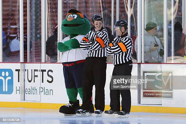 Wally the Green Monster jokes around with the referees before a Frozen Fenway NCAA Men's Division 1 hockey game between the Boston University...