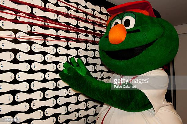 Wally the Green Monster signs the Wall of Fame Tuesday April 17 at the MLB Fan Cave located on Broadway and 4th Street in New York City