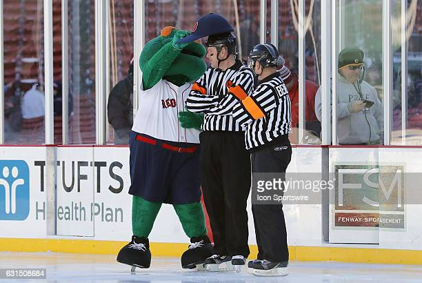 Wally the Green Monster slips his Red Sox cap on a referee before a Frozen Fenway NCAA Men's Division 1 hockey game between the Boston University...