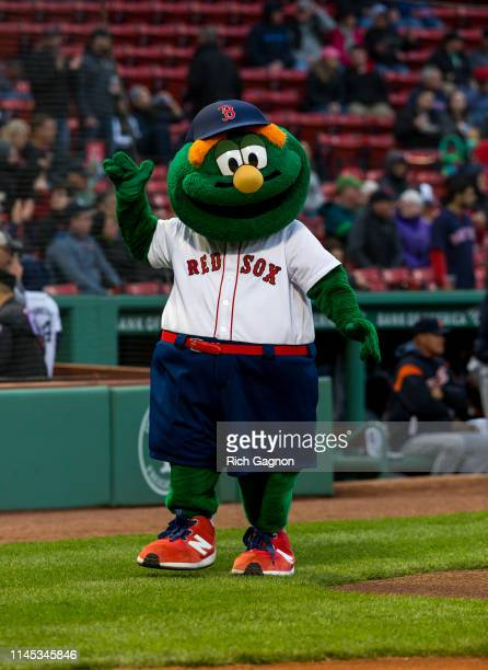 Wally the Green Monster the official mascot of the Boston Red Sox waves to the fans before a game against the Detroit Tigers at Fenway Park on April...