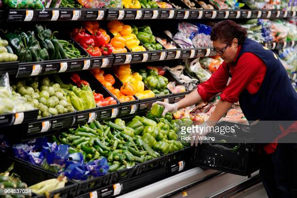 Walmart associate restocks fresh vegetables at a Walmart Supercenter during the annual shareholders seeting event on May 31 2018 in Rogers Arkansas...