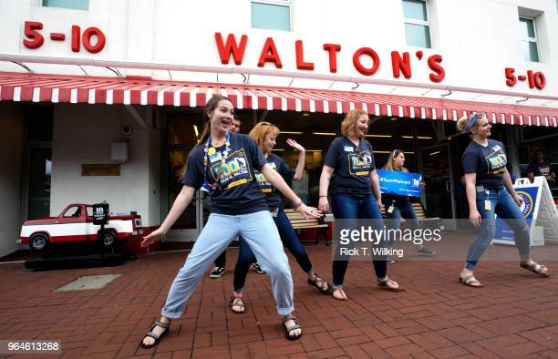 Walmart associates dance in front of Sam Walton's original 5 10 store now a museum during the annual shareholders meeting event on May 31 2018 in...