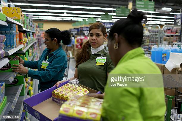 Walmart employee Yanetsi Grave and her fellow employees stock the shelves at a Walmart store on February 19 2015 in Miami Florida The Walmart company...