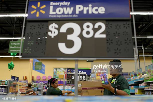 Walmart employees Clara Martinez and Saray Arrozarena stock the shelves at a Walmart store on February 19 2015 in Miami Florida The Walmart company...