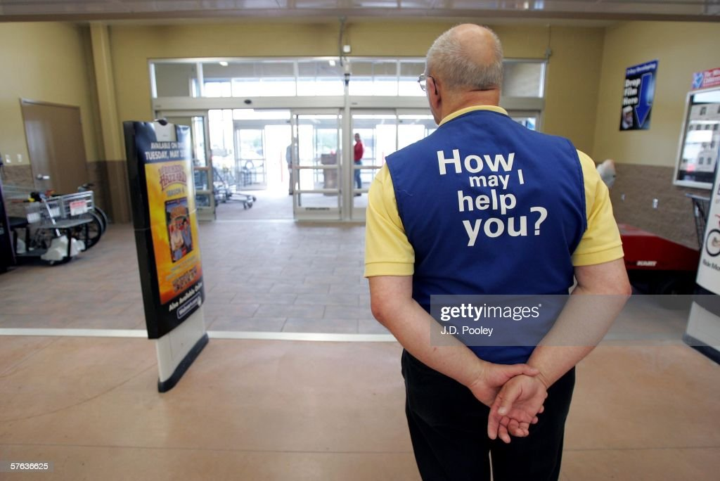 A Wal-Mart greeter waits to welcome new customers to the new 2,000 square foot Wal-Mart Supercenter store May 17, 2006 in Bowling Green, Ohio. The new store, one of three new supercenters opening today in Ohio, employs 340 people with 60 percent of those working full-time.