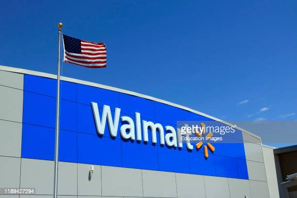 Wal-Mart logo on the store front of a store with American flag flying in front.