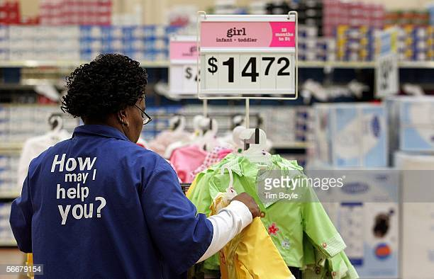 WalMart sales associate Cherry Williams from Chicago arranges girl infant/toddler clothing at the new WalMart store January 26 2006 in Evergreen Park...