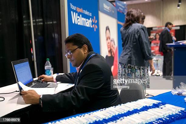 WalMart Stores Inc job recruiter Jayesh Hirani enters job seekers' resume information into a computer at the Black Data Processing Associates career...