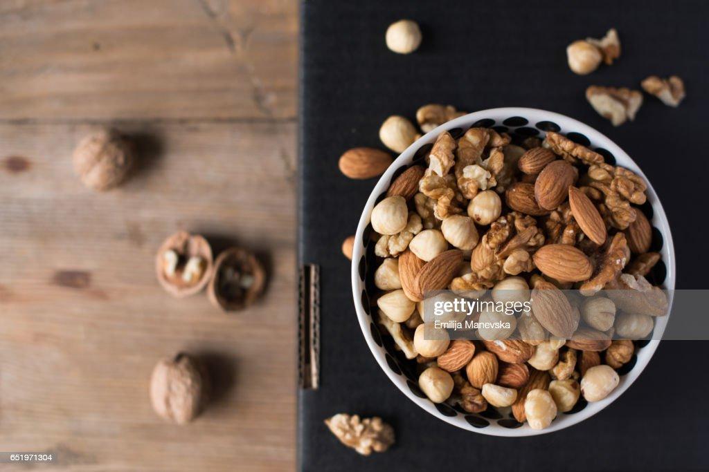 Walnuts, almonds and hazelnuts in a bowl on black background : Stockfoto