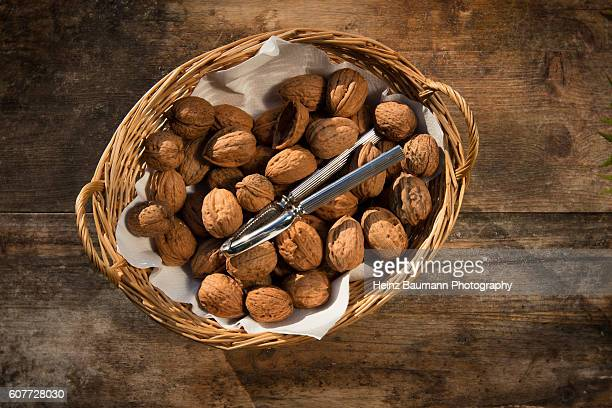 Walnuts and nutcracker in a basket on a weathered garden table