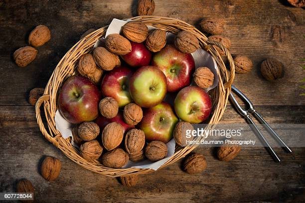 Walnuts and spartan apples in a basket on a weathered garden table