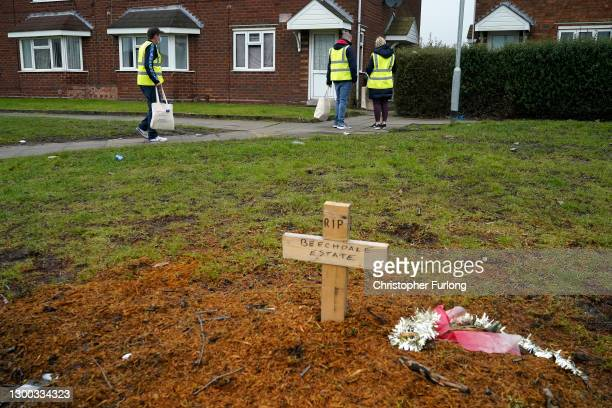 Walsall council staff walk past a makeshift memorial for a felled tree, as they begin delivering Covid-19 testing kits in the Beechdale area of...