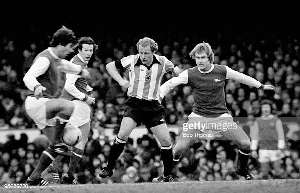 Walsall striker Alan Buckley is surrounded by Arsenal's Malcolm MacDonald Liam Brady and David Price during the FA Cup 5th round match at Highbury in...