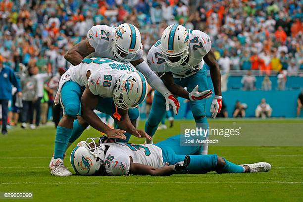 Walt Aikens of the Miami Dolphins is congratulated by Leonte Carroo Jordan Lucas and Isa AbdulQuddus after returning an attempted PAT by the Arizona...