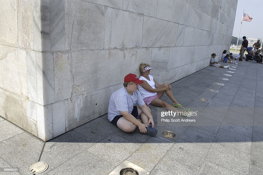 Walt and Cathy Prince, up from Mississippi, take shelter from the heat in the shadow of the Washington Monument. Temperatures in Washington D.C. are expected to climb to around 100 degrees this week.