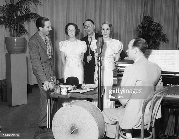 Walt Disney accepts a magazine award for his animated film of the Three Little Pigs Along to perform the music are composer Frank Churchill and the...