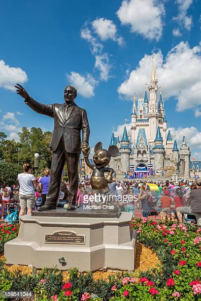 Walt Disney and Mickey Mouse statue in front of castle at Magic Kingdom Walt Disney World.