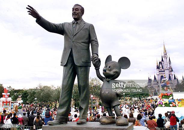 Walt Disney and Mickey Mouse statues stand at the Tokyo Disneyland in Urayasu city suburban Tokyo while visitors enjoy Disney characters' parade 13...