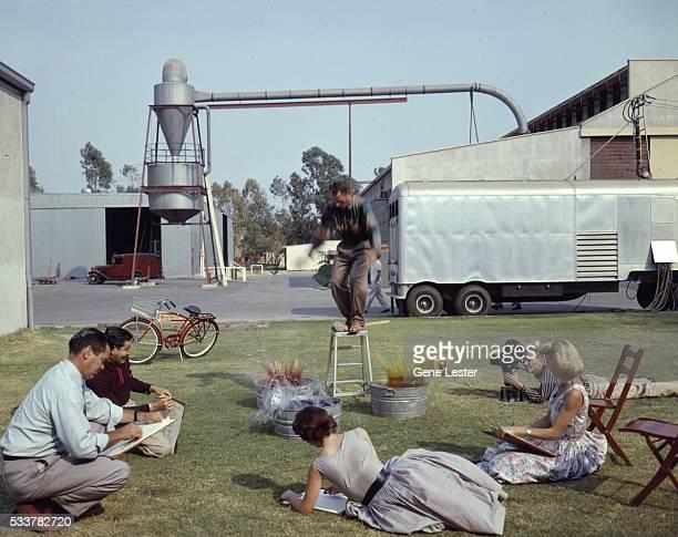 Walt Disney animators sketching together at Disneyland in circa 1955 in Anaheim California