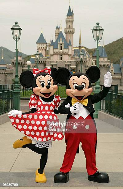 Walt Disney caracters Mickey Mouse and Minnie Mouse pose in front of the Sleeping Beauty Castle at the Disneyland theme park in Hong Kong 20 July...