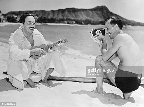 Walt Disney celebrated cartoonist and the creator of Mickey Mouse is shown on the beach at Waikiki playing on a ukulele while his brother and...