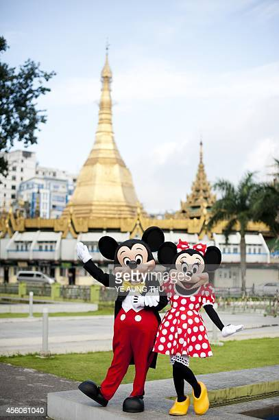 Walt Disney characters Mickey Mouse and Minnie Mouse pose for photographs in front of the Sulae Pagoda in Yangon on September 25 2014 The Disney...