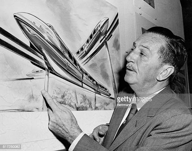 Walt Disney examines an artist's drawing of the futuristic Monorail system which will be in operation at Disneyland in June of this year