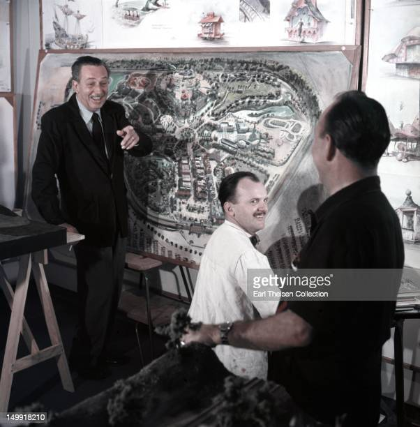 Walt Disney stands by a plan of Disneyland and chats with some imagineers circa 1954 in Los Angeles California