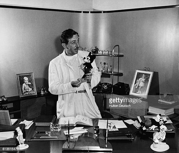 Walt Disney stands in his office holding his famous creation Mickey Mouse